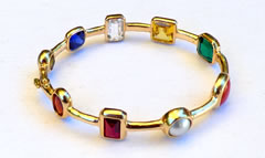 nine gem bangle in gold with chakra design