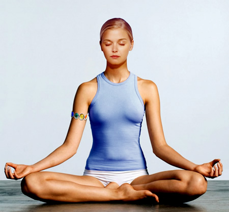 woman in lotus pose meditating with astrological gem bangle